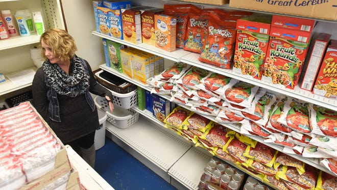Executive Director Jamie Trout talks about Eastside Community Ministry's food needs after donations of cereal refilled the cereal shelf. Despite the donation, the food pantry will need more in a few weeks.