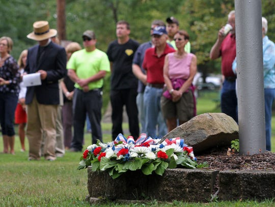 A wreath lays at the flag pole as the Borough of Peapack-Gladstone