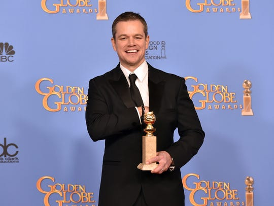 Matt Damon poses with his award for 'The Martian'
