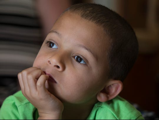 Corey, 6, sits in the room where he and his family