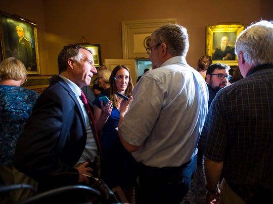 Gov. Phil Scott, left, answers questions after he and Senate President Pro Tempore Tim Ashe and Speaker of the House Mitzi Johnson announced a new state budget and school employee health care deal at the Statehouse in Montpelier on Wednesday, June 21, 2017.