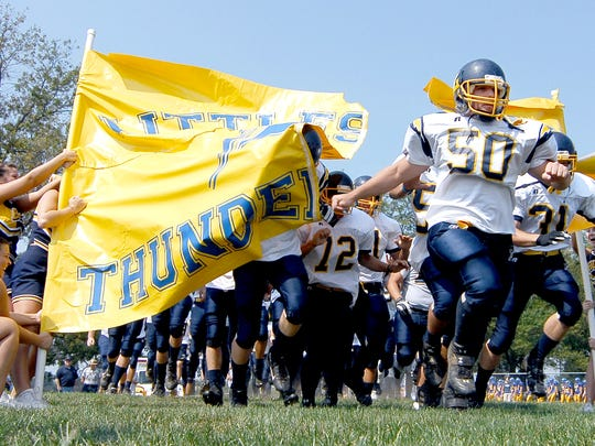 Littlestown senior Tyler Zittle leads his Littlestown Thunderbolts through the banner and onto the field for their game against the Kennard Dale Rams in 2007. The nickname Thunderbolts has roots with one of the school's former football coaches.