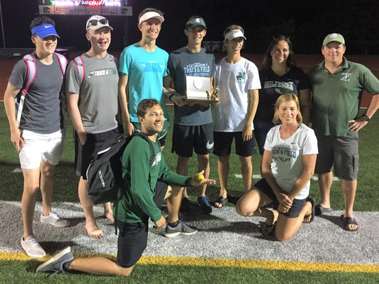Novi athletes and coaches hold the Oakland County Meet runner-up trophy.