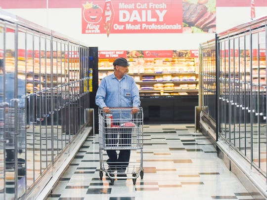 A customer browses the frozen food section of King Saver on the day of the new grocery store's grand opening on Thursday.