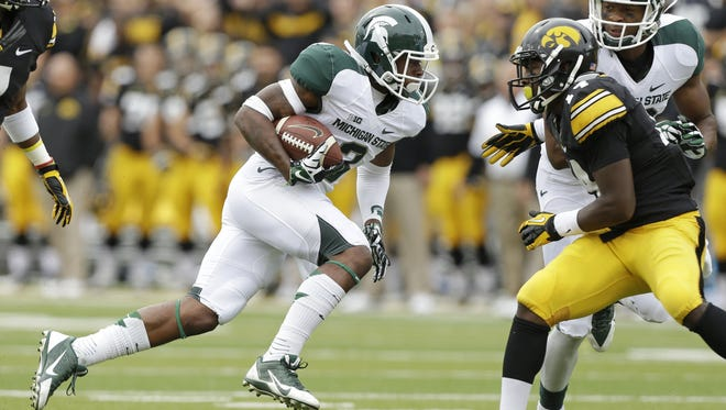 Michigan State wide receiver Macgarrett Kings Jr., left, runs from Iowa defensive back Desmond King (Detroit) on Oct. 5, 2013, in Iowa City, Iowa.