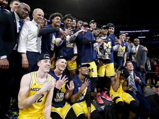 Michigan players and coaches celebrate after a 58-54 win over Florida State in an NCAA men's college basketball tournament regional final Saturday, March 24, 2018, in Los Angeles. (AP Photo/Alex Gallardo)