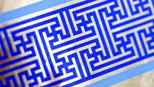 Cheryl Shapiro displays the Hanukkah gift wrap with a swastika-like pattern she found at Walgreens in Northridge, Calif., Monday,  Dec. 8, 2014.  The wrapping paper has been recalled from stores nationwide.