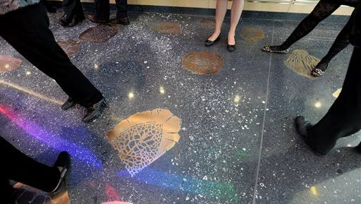 This undated photo shows the fossil terrazzo floor in the inside the lobby of the new C.S. Mott Children's Hospital in Ann Arbor, Mich. An app featuring a bronze fossil floor at the main entrance of the building allows patients to take virtual prehistoric journey.