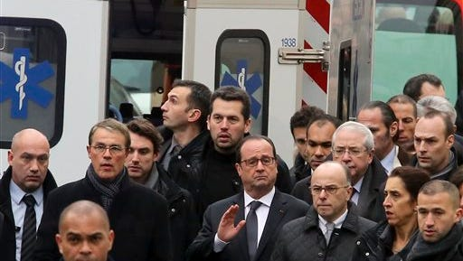 Surrounded by security, French President Francois Hollande, arrives at the office of French satirical newspaper Charlie Hebdo  in Paris on  Wednesday, Jan. 7, 2015. Masked gunmen stormed the offices Wednesday, killing at least a dozen people before escaping, police and a witness said. The weekly has previously drawn condemnation from Muslims because of its cartoons and spoofs of Islam's holiest figure, Muhammad.