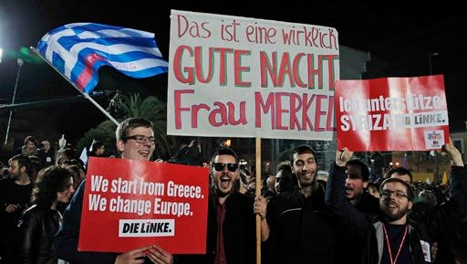 "Supporters hold placards as they show their support to Alexis Tsipras, leader of Syriza left-wing party, after his speech in central Athens, late Sunday, Jan. 25, 2015. The placard, center, reads in German: 'This is really a goodnight Mrs Merkel' referring to the German chancellor, and the right one reads: 'I support Syriza, Die Linke,' referring to another leftist party.  A triumphant Tsipras told Greeks that his radical party's win in Sunday's early general election meant an end to austerity and humiliation and that the country's regular debt inspections were a thing of the past. ""Today the Greek people have made history. Hope has made history,"" he said in his victory speech."