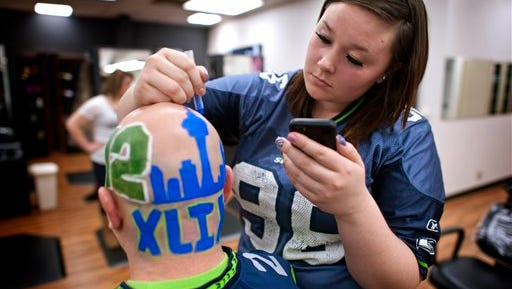 Brian Evensen, an teacher at Walla Walla (WA) Community College, gets the back of his head painted with the Seattle skyline Friday morning, Jan. 30, 2015, at the hands of student Makiah Steen. The cosmetology department was busy with school and community members coming by for free Hawkmania make-overs. (AP Photos/Walla Walla Union-Bulletin, Greg Lehman)