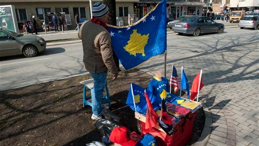 A street vendor displays Kosovo and Albanian flags along with other paraphernalia for sale in the Kosovo capital of Pristina on Monday, Feb. 16, 2015. Festivities marking the seventh  anniversary of Kosovo's Independence from Serbia have been kept low-key amid growing social discontent.
