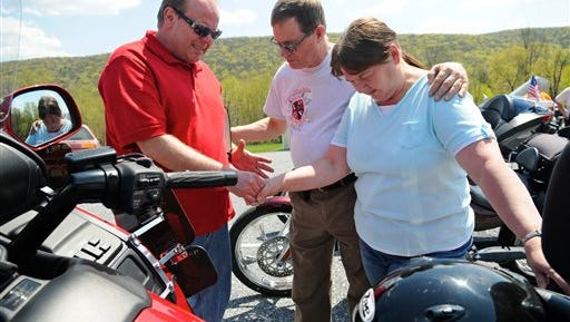 AP File Photo: Calvary Independent Church pastor Robert Straub, left, blesses Free Wheelers Motorcycle Club members Danny and Diane Overkott, of Ashland, Pa., with their Honda motorcycles in the parking lot of the church during the annual Blessing of the Bikers in Lykens, Pa., Sunday, May 3, 2015. (Jacqueline Dormer/Republican-Herald via AP) MANDATORY CREDIT