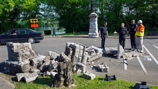 Officials view the remnants of a more than 100-year-old stone column that was toppled in the Island Home Park neighborhood Thursday, May 7, 2015, in Knoxville, Tenn. The column was struck by a tractor-trailer that was attempting to make a delivery to a nearby business. (Paul Efird/Knoxville News Sentinel via AP)