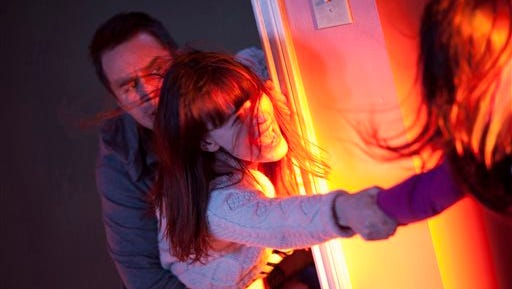 "This photo provided by Twentieth Century Fox shows, Sam Rockwell, left, as Eric Bowen and Rosemarie DeWitt, center, as wife Amy, desperately trying to hold on to Kennedi Clements, right, their youngest daughter Madison, who's been targeted by terrifying apparitions in the film, ""Poltergeist."" (Kerry Hayes/Twentieth Century Fox  via AP)"
