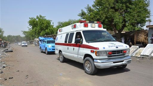 An ambulance and security cars drive to the  site of  a suicide bomb attack at a  market in Maiduguri, Nigeria, Tuesday, June 2, 2015.  Boko Haram attacked the northeastern Nigerian city of Maiduguri on Tuesday with deafening explosions from the west and a suicide bombing near the center that witnesses said killed as many as 20 people.  (AP Photo/Jossy Ola)