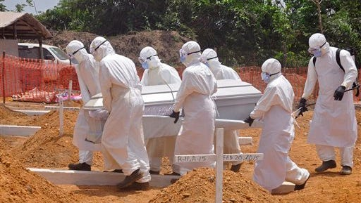 FILE - In this file photo taken on Wednesday, March 11, 2015,  health workers carry a body of a person that they suspected died form the Ebola virus at a new graveyard on the outskirts of Monrovia, Liberia. The corpse of a 17-year-old man has tested positive for Ebola in Liberia, but no other cases have been reported, the country's deputy health minister said late Monday, June 29, 2015.  (AP Photo/ Abbas Dulleh,File)
