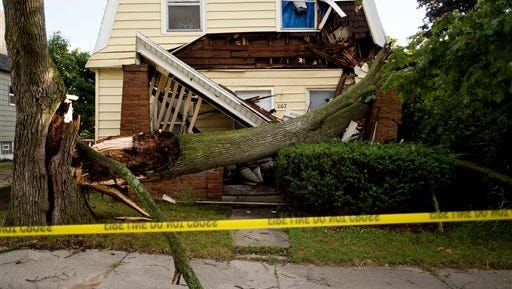 A fallen tree rests on a damaged home after a storm passed on Sunday in Grand Rapids, Mich., Monday, Aug. 2, 2015.   Storms carrying strong winds and rain have pummeled Michigan, cutting power and snapping trees. (Neil Blake /The Grand Rapids Press via AP)