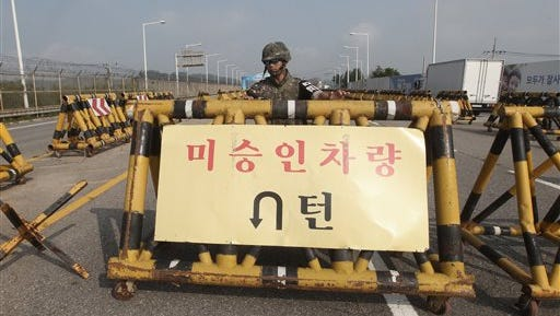 "A South Korean amy soldier stands guard behind a barricade on Unification Bridge, which leads to the demilitarized zone, near the border village of Panmunjom in Paju, South Korea, Saturday, Aug. 22, 2015. The letters at a banner read "" Disapproved Vehicles"".  South Korea and North Korea agreed Saturday to hold their first high-level talks in nearly a year at a border village to defuse mounting tensions that have pushed the rivals to the brink of a possible military confrontation. (AP Photo/Ahn Young-joon)"