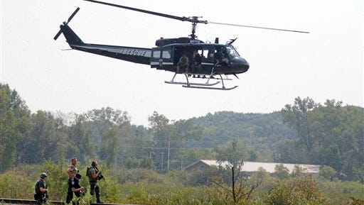 Police on foot and in the air search for suspects in the shooting of a police officer Tuesday, Sept. 1, 2015  in Fox Lake, Ill. Fox Lake Police Lt. Charles Joseph Gliniewicz was shot and killed while pursuing a group of suspicious men. Police with helicopters, dogs and armed with rifles are conducting a massive manhunt in northern Illinois for the individuals believed to be involved in the death of the three-decade member of the department and a father of four sons. (Brian Hill/Daily Herald, via AP)  MANDATORY CREDIT, MAGS OUT