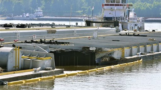 Damage on a barge is seen as it is moored along the Kentucky shore of the Mississippi River at Columbus-Belmont State Park in Columbus, Ky., Thursday, Sept. 3, 2015. A tow, seen in the background, traveling north on the river struck the barge as it was traveling south across the river. The Mississippi River has been closed to barge traffic because the damaged barge leaked clarified slurry oil. (AP Photo/Stephen Lance Dennee)