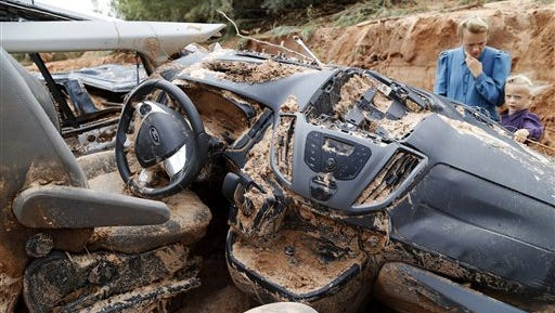A woman and child examine a vehicle swept away during a flash flood, Tuesday, Sept. 15, 2015, in Hilldale, Utah. Authorities say several people have died in flash flooding that swept away vehicles on the Utah-Arizona border. (Michael Chow/The Arizona Republic via AP)  MARICOPA COUNTY OUT; MAGS OUT; NO SALES; MANDATORY CREDIT