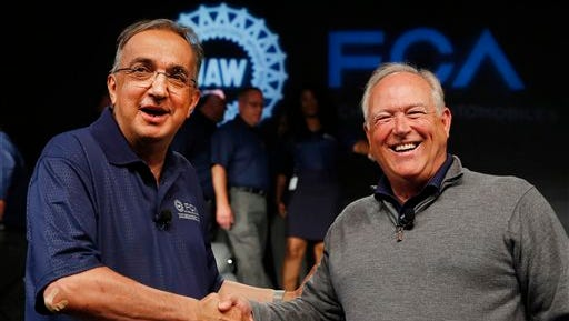 FILE - In this July 14, 2015, file photo, Fiat Chrysler Automobiles CEO Sergio Marchionne, left, and United Auto Workers President Dennis Williams shake hands during a ceremony to mark the opening of contract negotiations in Detroit. The United Auto Workers union and Fiat Chrysler have reached a tentative deal on a new contract for about 40,000 workers that will serve as a pattern for pacts with General Motors and Ford. Terms of the deal were not disclosed Tuesday, Sept. 15, but both sides said a news conference would be held later in the evening with Williams and Marchionne. (AP Photo/Paul Sancya, File)