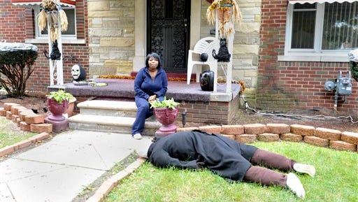 Jeannine Haddon poses on the porch of her Halloween decorated home, Friday, Oct. 9, 2015, in Detroit. The dummy placed face down in her front yard as a Halloween prank has prompted repeated visits by police.