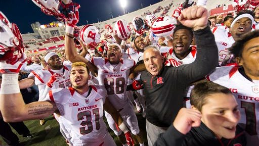 Rutgers head coach Kyle Flood joins his players as they sing the school song to their fans in the stands after defeating Indiana 55-52 in an NCAA college football game, Saturday, Oct. 17, 2015, in Bloomington, Ind. (AP Photo/Doug McSchooler)