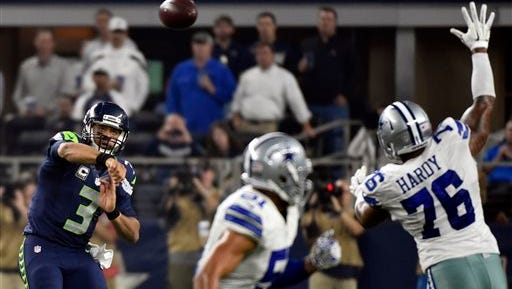 Seattle Seahawks' Russell Wilson (3) passes the ball past Dallas Cowboys' Greg Hardy (76) in the second half of an NFL football game Sunday.