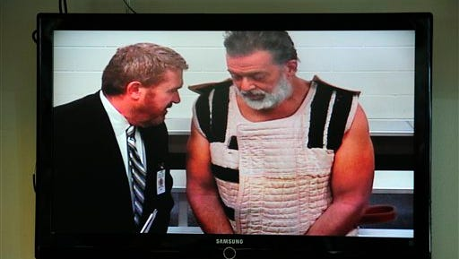 In this Nov. 30 photo, Colorado Springs shooting suspect, Robert Dear, right, appears via video before Judge Gilbert Martinez, with public defender Dan King, at the El Paso County Criminal Justice Center for this first court appearance, where he was told he faces first degree murder charges, in Colorado Springs, Colo. The man accused of killing three people at a Colorado Planned Parenthood clinic brought several guns, ammunition and propane tanks that he assembled around a car. To some in the community, the attack resembled an act of domestic terrorism, sparking a debate over what to call Robert Lewis Dear's rampage even before he was taken into custody.