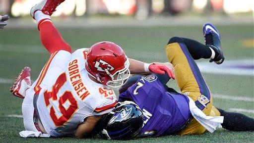 Kansas City Chiefs defensive back Daniel Sorensen, left, tackles Baltimore Ravens quarterback Jimmy Clausen on Sunday.