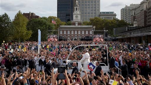 In this Sept. 26, 2015, file photo, Pope Francis rides in the popemobile along Independence Mall before delivering a speech outside Independence Hall in Philadelphia. Amid the whirlwind came an historic visit in 2015. Pope Francis attracted throngs during a two-day trip in September. Many pilgrims were thrilled to see him celebrate an outdoor Mass and hear his remarks on immigration and religious liberty at Independence Hall.