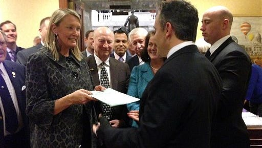 Republican state Sen. Julie Raque Adams, left, hand delivers an abortion bill to Republican Gov. Matt Bevin on Tuesday, Feb. 2, 2016 in Frankfort, KY. The bill requires women to have a face-to-face consult with a doctor 24 hours before having an abortion. Bevin immediately signed the bill, his first as governor. (AP Photo/Adam Bevin)