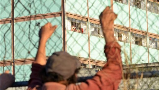 A man holds on to a fence surrounding the Topo Chico prison, where a riot broke out around midnight, in Monterrey, Mexico, Thursday, Feb. 11, 2016.