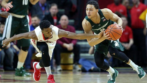 Rutgers guard Omari Grier, left, tries to make a steal as Michigan State guard Bryn Forbes tries to control the ball during the first half.