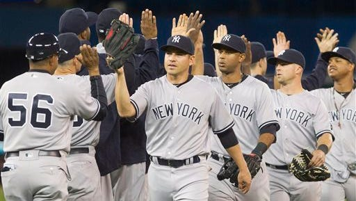 New York Yankees celebrate after defeating the Toronto Blue Jays in a baseball game Tuesday, April 12, 2016, in Toronto. The Yankees won 3-2.