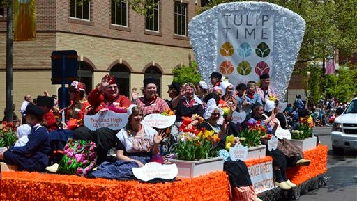 The Dutch Dance Directors wave from their float in the Volksparade during the annual Tulip Time Festival in Holland on Wednesday, May 11, 2016.