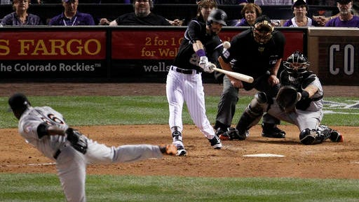 Colorado Rockies' David Dahl (26) hits an RBI double off Miami Marlins relief pitcher Fernando Rodney during the eighth inning of a baseball game in Denver on Friday, Aug. 5, 2016. (AP Photo/Joe Mahoney)