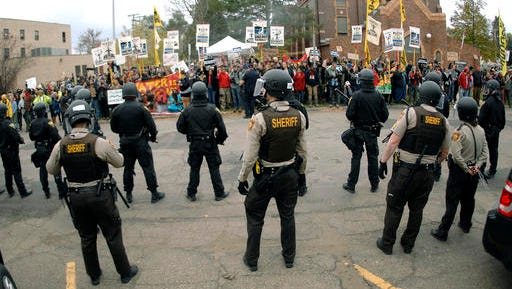 Law enforcement officers line the street in front of the Morton County Courthouse in Mandan, N.D., as Dakota Access Pipeline protesters stand on the opposite side of the street on Monday, Oct. 17, 2016. The protesters gathered in support of journalist Amy Goodman before her court hearing on a rioting charge while covering the protesters in September. A SouthCentral District judge dismissed the charge.  (Mike Mccleary/The Bismarck Tribune via AP)