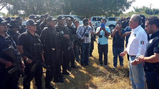 In this photo released by Guerrero state Attorney Generals Office, Javier Olea, attorney general of Guerrero state, right, talks to police at the start of a security operation in San Jeronimo El Grande, Mexico, Thursday, Nov. 24, 2016.  Soldiers and police fanned out Friday across Guerrero state, chasing a wounded gang leader and trying to quell a wave of violence that included the discovery of hidden graves holding dozens of bodies and a camp where gunmen stored the severed heads of nine rivals in a cooler.