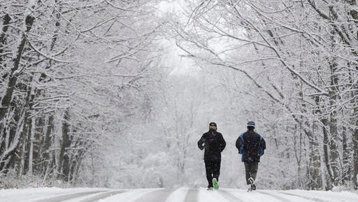 Ken Perry and Stan Ly go for a run in Eagle Creek Park as snow falls Tuesday, Dec. 13, 2016, in Indianapolis.