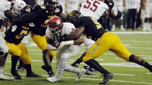 North Carolina Central running back Dorrel McClain is surrounded on the tackle by Grambling State defenders during the first half of the Celebration Bowl College football game at the Georgia Dome in Atlanta on Saturday.