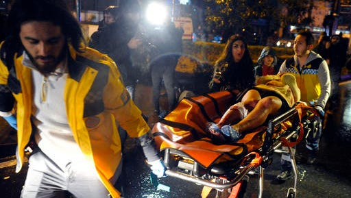 FILE - In this Sunday, Jan. 1, 2017 file photo, medics carry a wounded person at the scene after an attack at a popular nightclub in Istanbul. Survivors of the massacre at a Turkish nightclub describe an hour of pure terror and how they escaped, by feigning death, rappelling to the sea, or hiding anywhere they could find. The Islamic State gunman fired 180 rounds for seven minutes, killing 39 people on New Year's Eve. He escaped after he wiped his Kalashnikov free of fingerprints, changed clothes, put on a Santa hat and blended into the crowd evacuating the bloody Reina nightclub.
