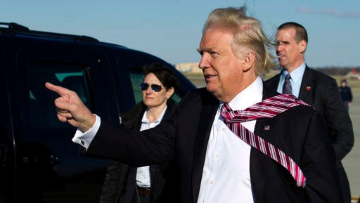 President Donald Trump points to guests upon his arrival at Andrews Air Force One, Md., Thursday, Jan. 26, 2017. Trump is returning from Philadelphia after speaking at the House and Senate GOP lawmakers at their annual policy retreat.