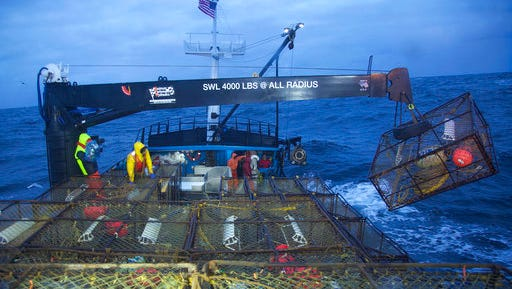 """This image released by Discovery Channel shows a crane removing a pot from the stack as the Summer Bay crew sets its gear in """"Deadliest Catch.""""  Climate change is one of the main characters in the new season of """"Deadliest Catch,"""" with the crab fishermen in one of Discovery's most enduring and popular shows forced to deal with a sudden warming of the Bering Sea that chases their prey into deeper, more dangerous water. The show's 13th season debuts Tuesday at 9 p.m. ET."""