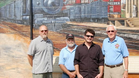 From left, Glen Rock Historic Preservation Society members Roger Butz and John 'Otts' Hufnagel; mural artist Marshall Adams; and Glen Rock Historic Preservation Society member Terry McFatridge stand in front of the railroad mural Adams painted on the building where the train station once stood. Hufnagel, who headed the preservation society died in 2016.
