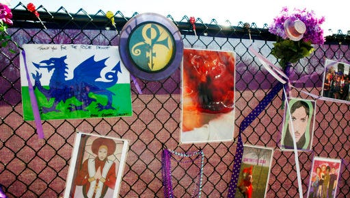 In this April 6, 2017, photo, fan artwork of Prince hangs on a new memorial fence in the parking lot of Paisley Park Museum, the former home and recording complex of the late superstar in Chanhassen, Minn. Affidavits and search warrants were unsealed in Carver County District Court Monday, April 17, 2017, as the yearlong investigation into Prince's death continues.