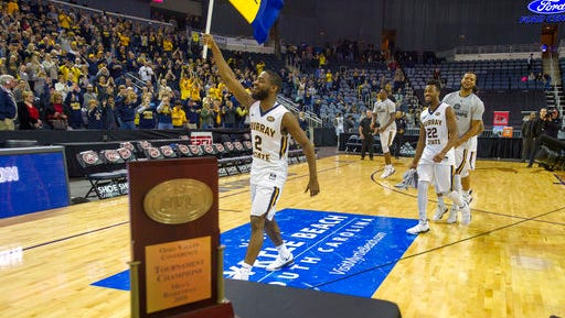 Murray State's Johnathan Stark (2) carries the school flag past the trophy table after his team won an NCAA college basketball game against Belmont in the championship of the Ohio Valley Conference tournament, Saturday, March 3, 2018, in Evansville, Ind. (AP Photo/Daniel R. Patmore)