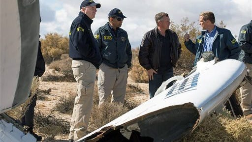 """In this Nov. 1, 2014, photo provided by the National Transportation Safety Board, Virgin Galactic pilot Todd Ericson, right, talks with NTSB Acting Chairman Christopher A. Hart, second from left, at the SpaceShipTwo accident site with investigators in Mojave, Calif. The cause of Friday's crash of Virgin Galactic's SpaceShipTwo has not been determined, but investigators found the """"feathering"""" system, which rotates the tail to create drag, was activated before the craft reached the appropriate speed, National Transportation Safety Board Acting Chairman Christopher Hart said. (AP Photo/NTSB)"""